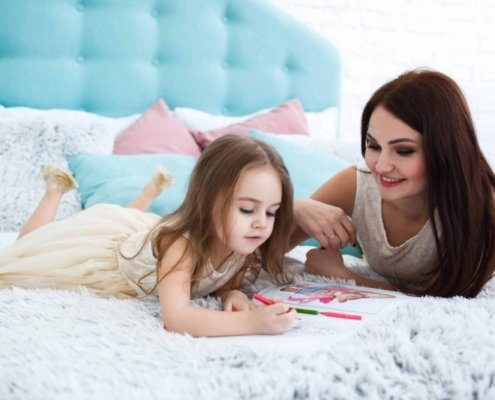 mother watching her toddler coloring something while lying on the bed