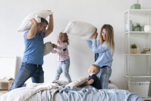 kids playing pillow fight with parents
