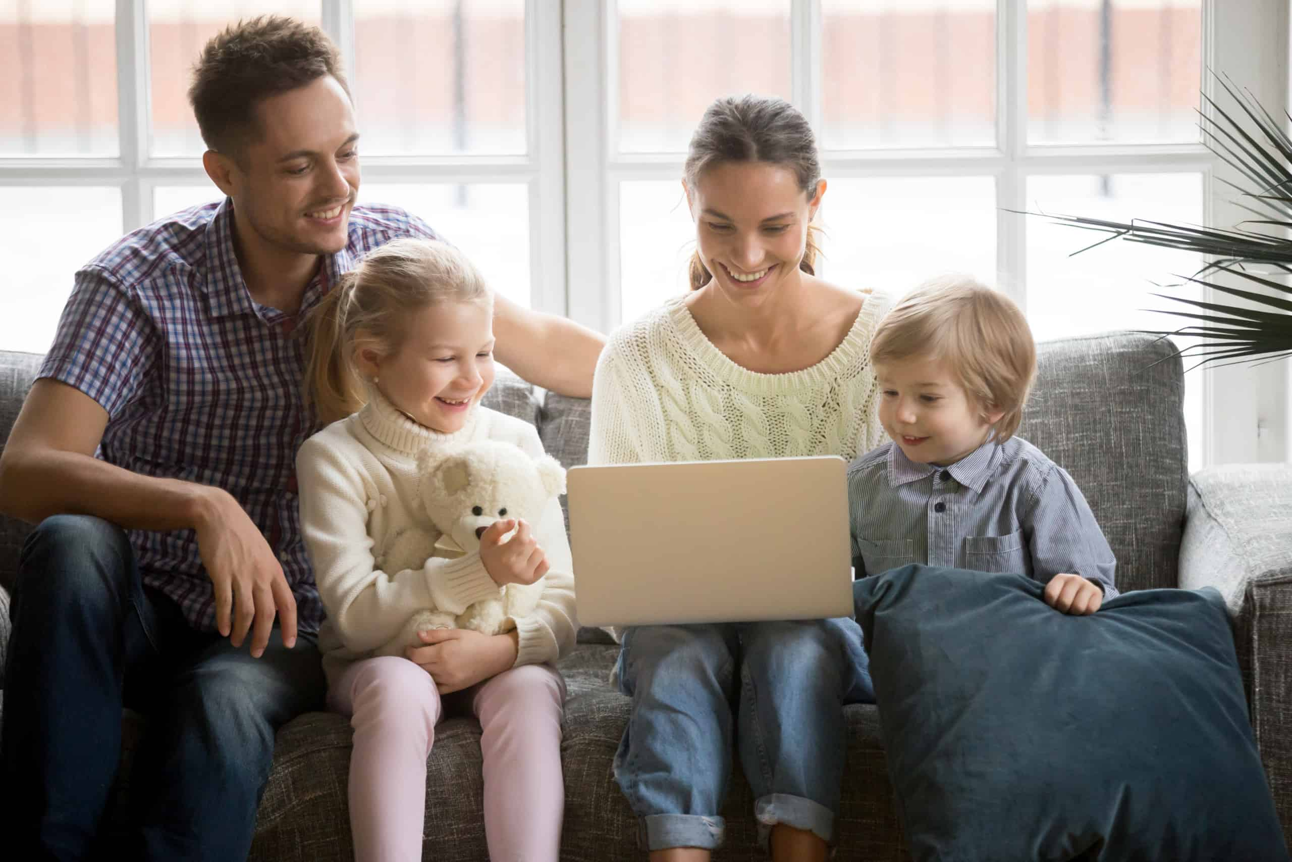 Happy family with children having fun using laptop on sofa