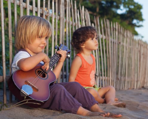 Little happy boy have fun, play music on Hawaiian guitar ukulele for small baby girl, enjoying sunset ocean beach. Children healthy lifestyle. Travel, family activity on tropical island summer holiday