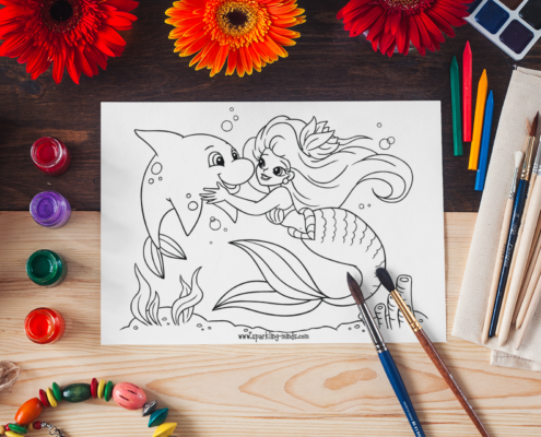 image of a mermaid coloring page for kids placed on a table surrounded by paint brushes